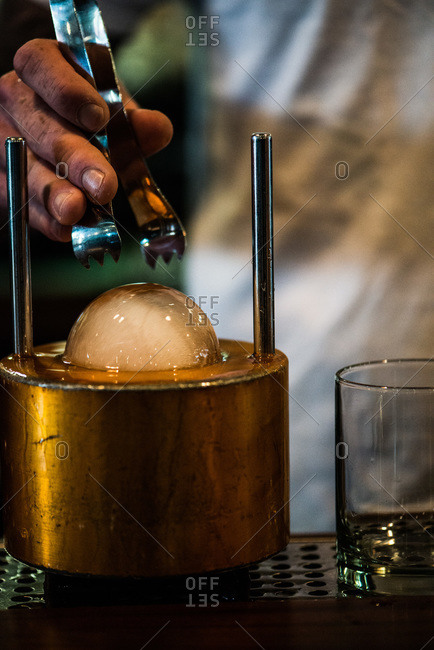Man preparing ice sphere for cocktail