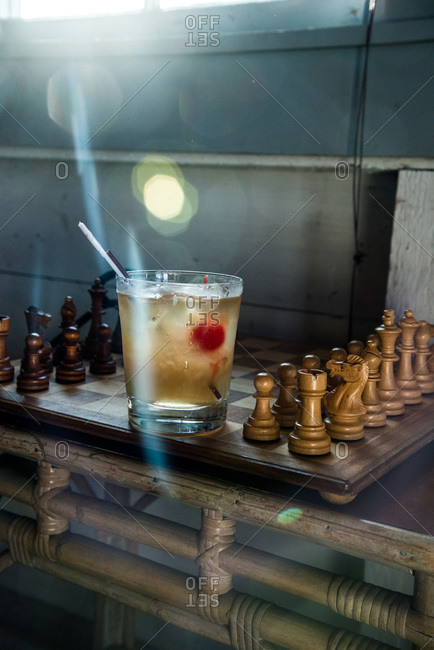 Cocktail with a maraschino cherry on a chessboard