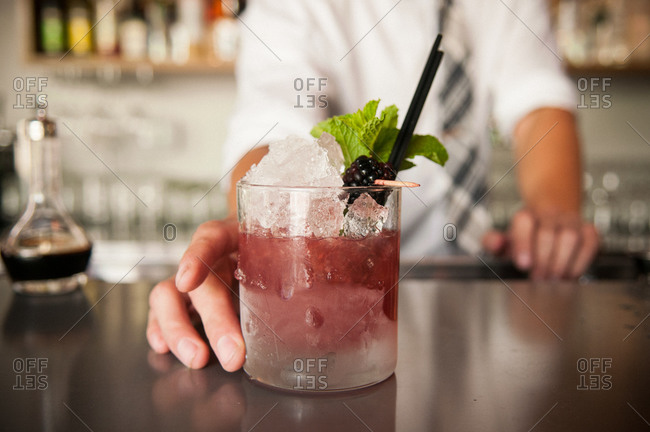 Berry cocktail on bar counter with bartender