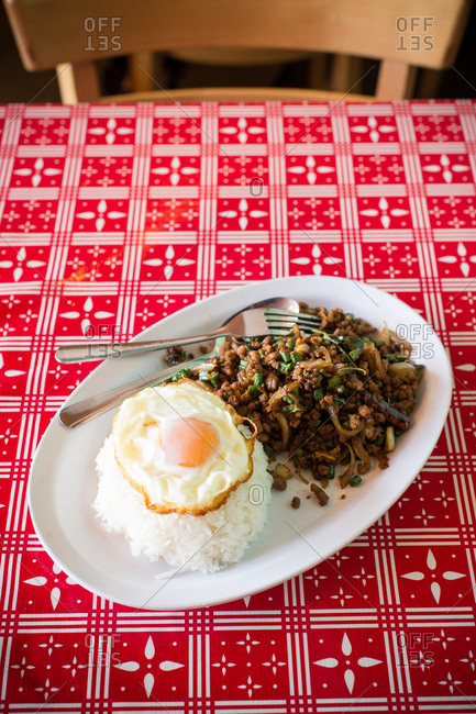 Thai noodles with egg and rice on red tablecloth