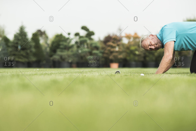 Golf player kneeling on turf looking at golf ball