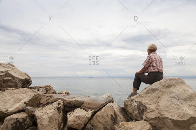 Woman sitting on rocks at waterside looking at horizon