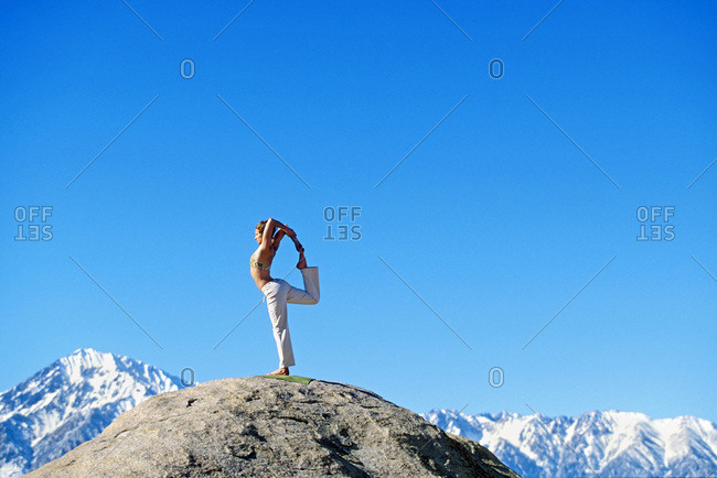 Woman displaying stength, balance, and focus in yoga pose on boulder in Buttermilk Country outside of Bishop, California with Mt.