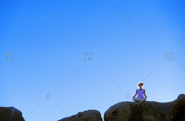 Silhouette of boulder and woman sitting, meditating in yoga pose on boulder in Buttermilk Country outside of Bishop, California.