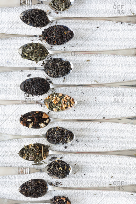 Spoons with tea varietals on textured fabric
