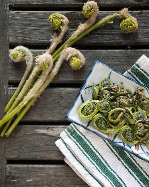 Overhead view of foraged fiddlehead ferns on rustic table
