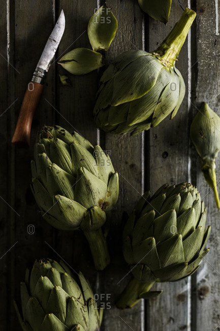 Several artichokes on a table with a knife