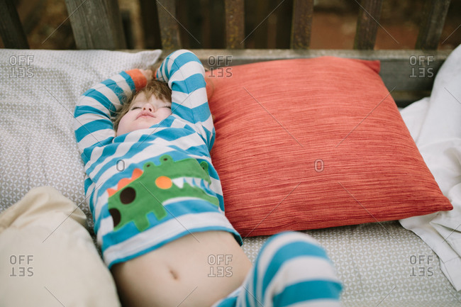 Girl napping on pillows on deck