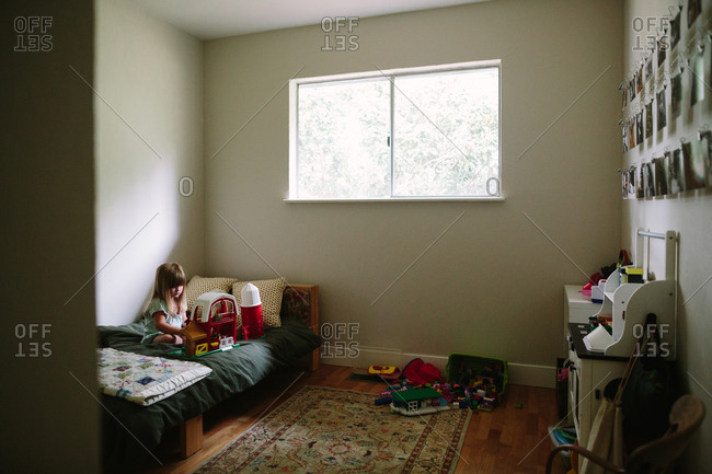 Girl playing with farm set in bedroom