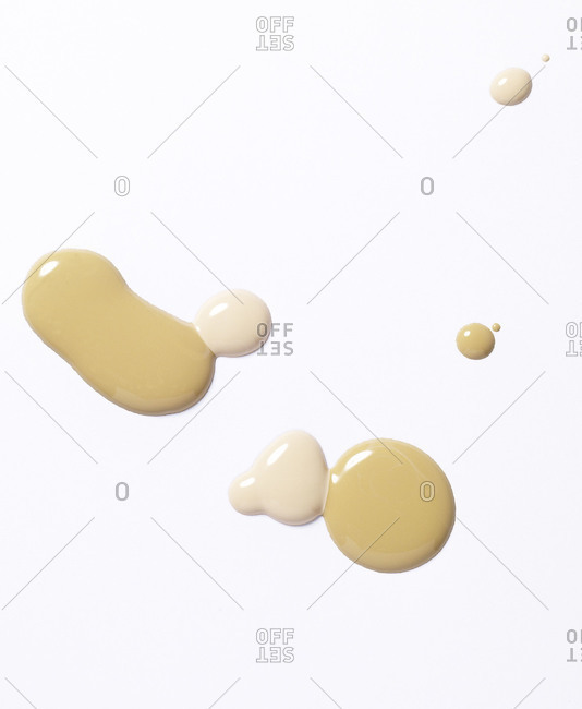 Splotches of beige and pink liquid foundation on white background