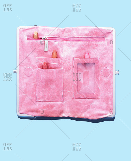 A pink purse with lipstick on white background