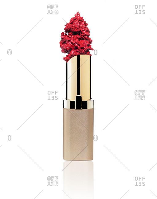 Lipstick tube with smashed lipstick on white background