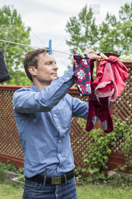 Stay at home dad removing clothes from clothesline at yard
