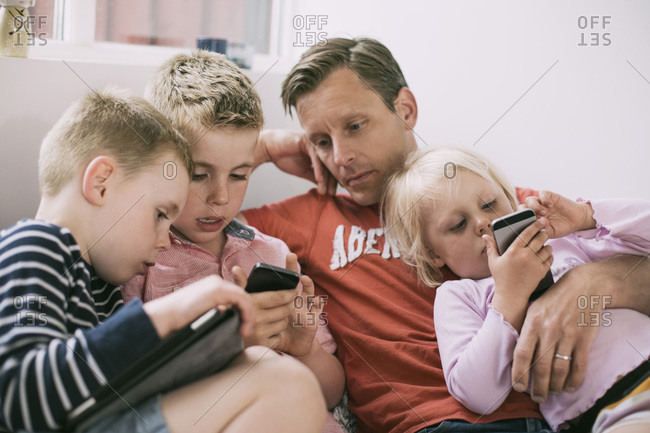 Father and children using technologies at home