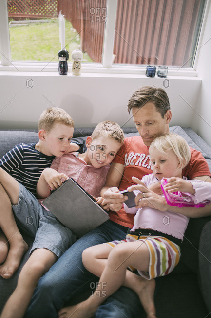 Father and children using technologies on sofa at home