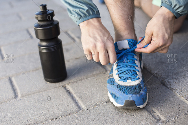 Low section of man tying sport shoelace by water bottle on street