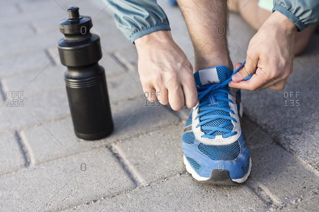 Low section of man tying sport shoelace by water bottle on street