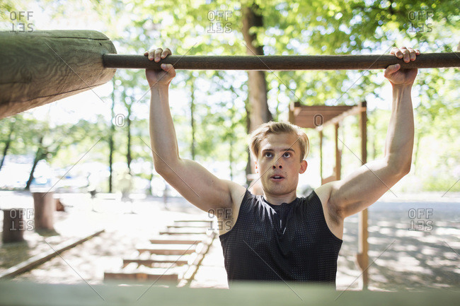 Determined man lifting wooden bar at outdoor health club