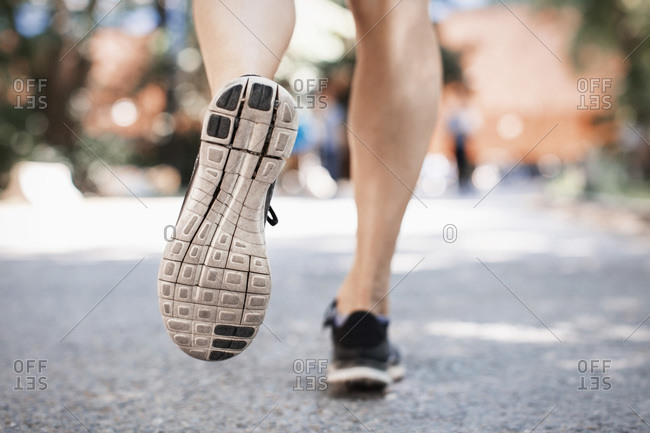Low section of woman in sports shoes running on park street