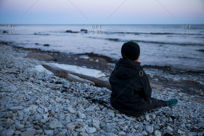 Rear view of boy looking at sea view while sitting on shore