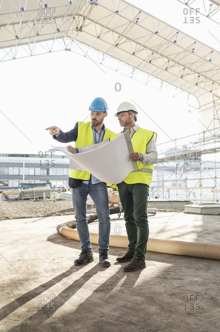 Experts discussing over blueprint at construction site
