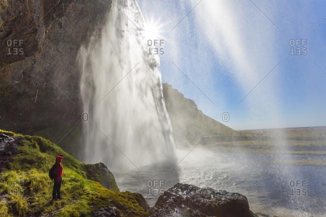 Person observing Seljalandsfoss waterfall in Iceland