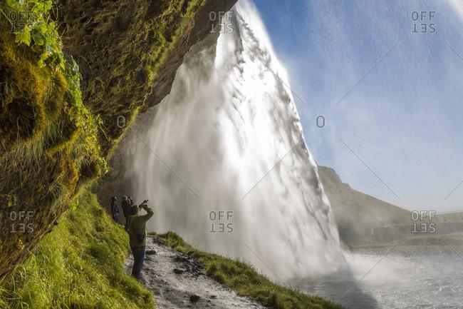 Seljalandsfoss Waterfall, Suourland, Iceland - August 21, 2014: Hikers observing Seljalandsfoss waterfall