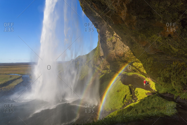 Hikers and  Seljalandsfoss waterfall in Iceland