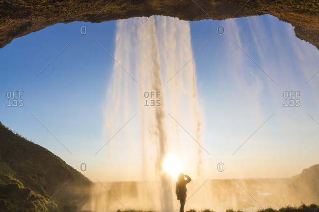 Hiker behind Seljalandsfoss waterfall in Iceland