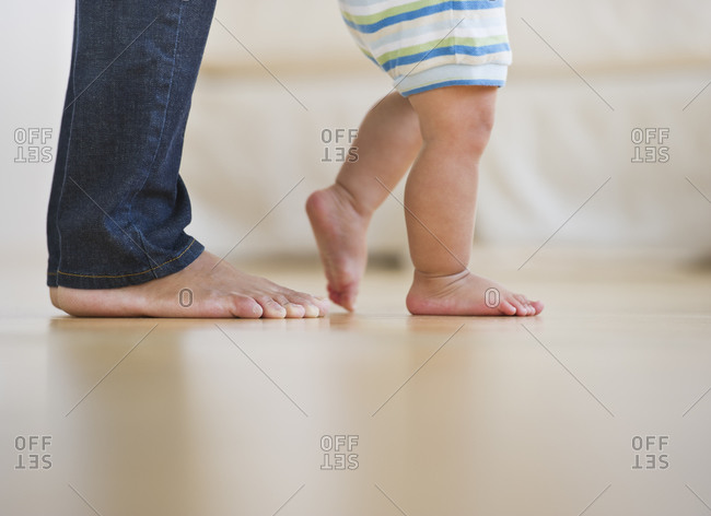 Mother assisting in her son's (6-11 months) first steps