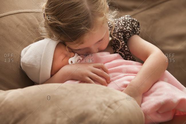 Girl (2-3) embracing baby sister on sofa