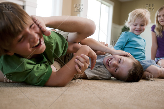 Children play fighting on floor