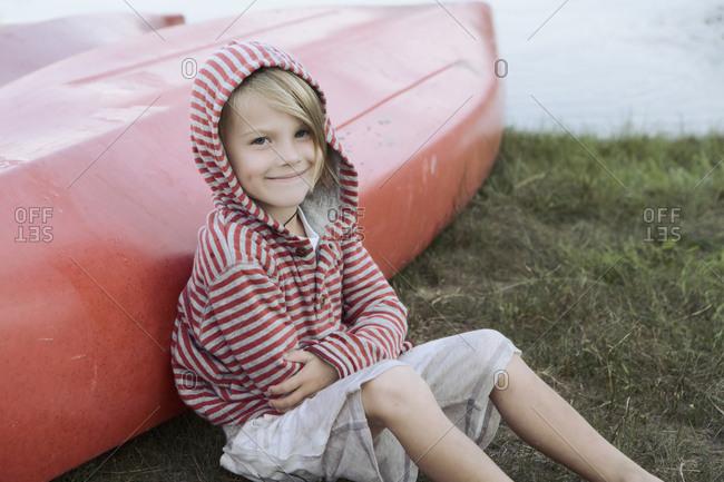 Portrait of boy (4-5) sitting by canoe