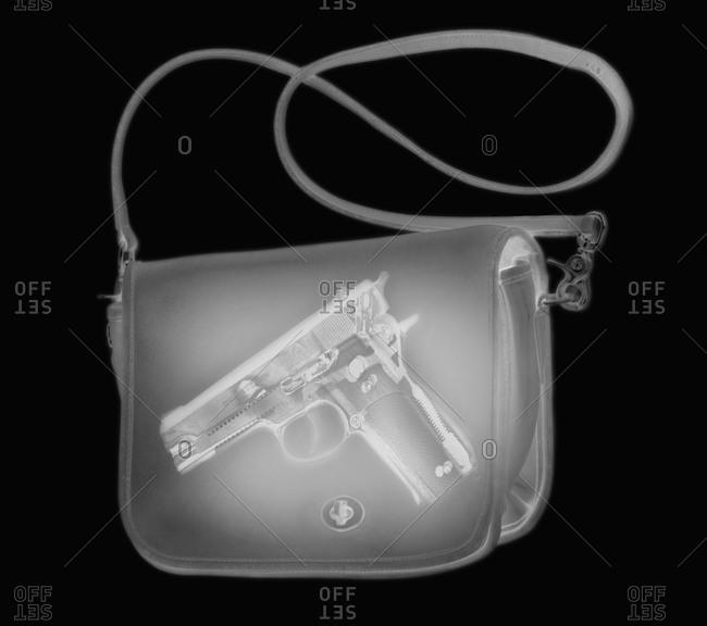 X-ray image showing handbag containing pistol