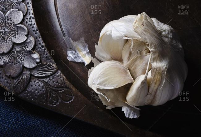 Torn garlic bulb on old wooden platter