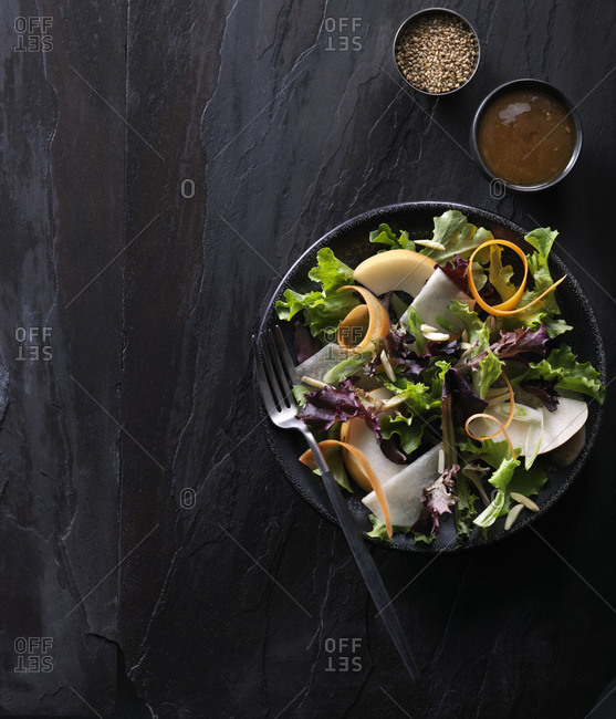 Overhead view of pear and arugula salad with balsamic dressing
