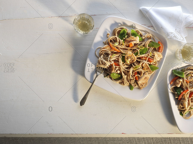 Overhead view of chicken and snow peas with whole wheat pasta