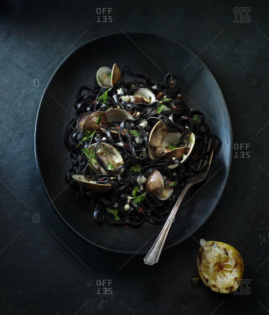 Clams in squid ink pasta on a plate