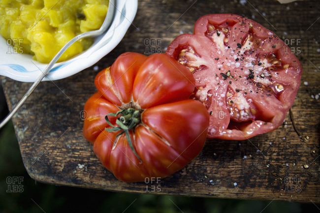 Halved heirloom tomato with salt and pepper