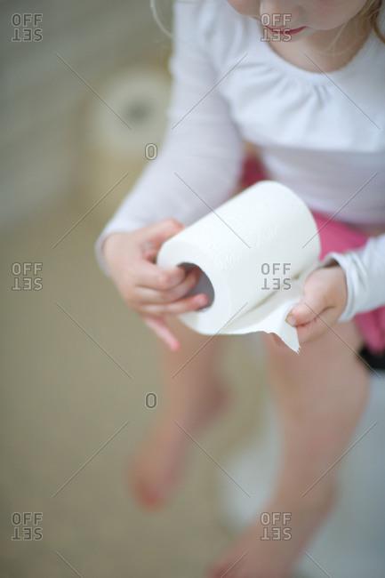 Little girl holding tissue paper in toilet