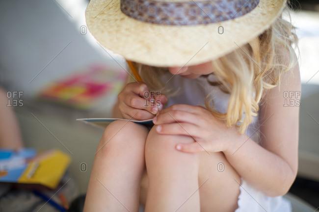 Little girl writing on book