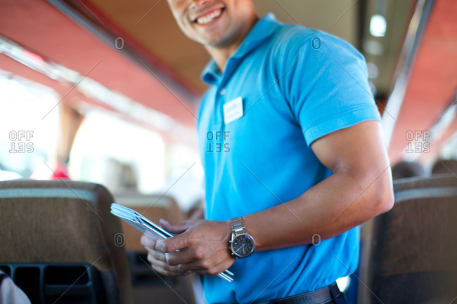 Man holding guide brochure in tour bus