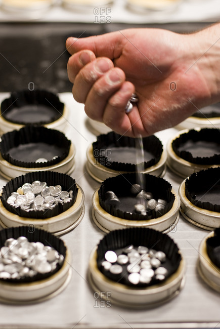 A chef drops sliver medallions into individual wrappers