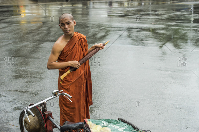 Yangon, Burma - September 20, 2014: A man holds an umbrella in the rain