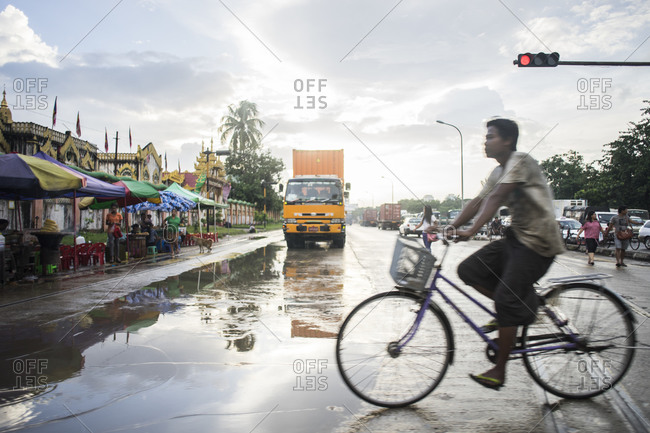 Yangon, Burma - September 20, 2014: A man rides his bike across the street