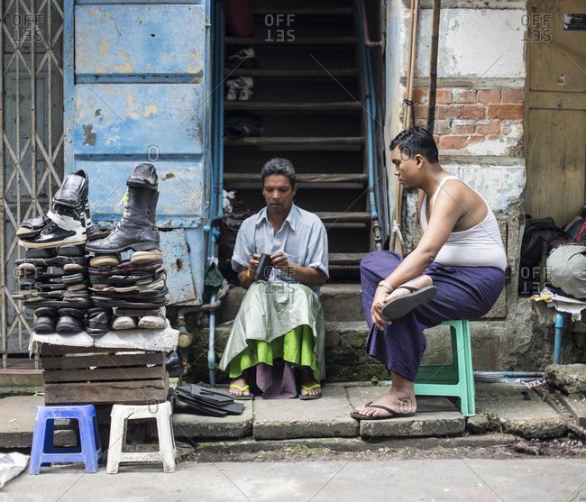 Yangon, Burma - September 23, 2014: A cobbler works on shoes on a stoop