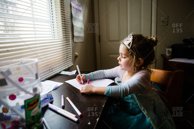 Girl drawing with markers in princess dress