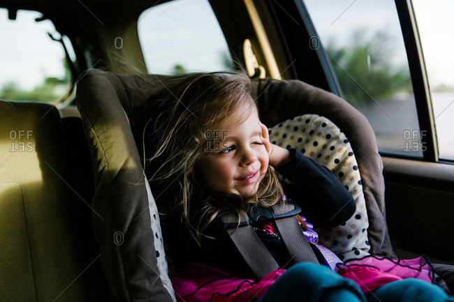 Girl in car seat squinting at sun