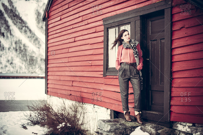Brunette woman standing at the entrance of a Norwegian hytte