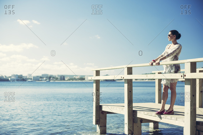 Brunette woman standing on a pier in Mallorca, Spain